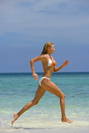 Stock Photo: 4286-66783 sexy blond woman jogging on tropical beach in  Krabi