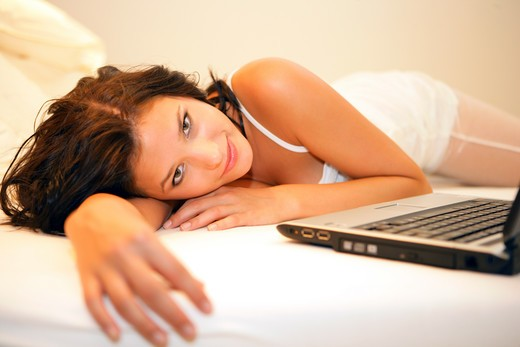 Stock Photo: 4286-67900 Young woman tired on bed with laptop