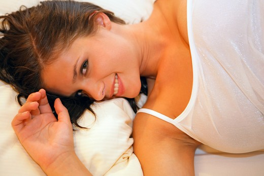 young woman relaxing in bed : Stock Photo
