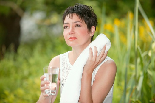 Stock Photo: 4286-68509 woman sitting in garden drinkin water