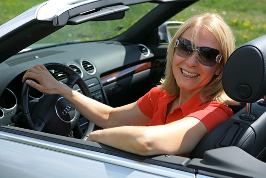 Stock Photo: 4286-68780 A senior woman driving cabriolet sportscar with roof down