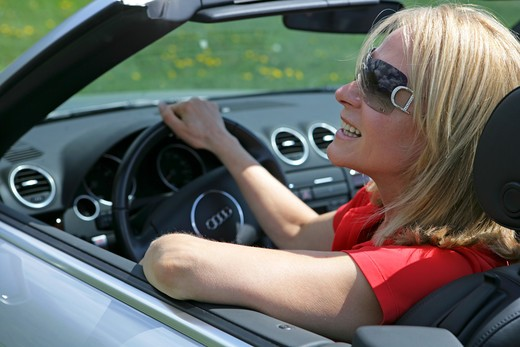 A senior woman driving cabriolet sportscar with roof down : Stock Photo