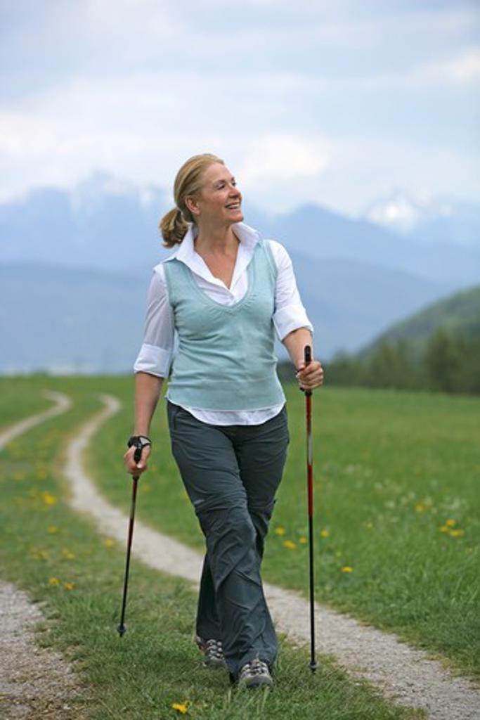 Blonde mature woman nordic walking : Stock Photo