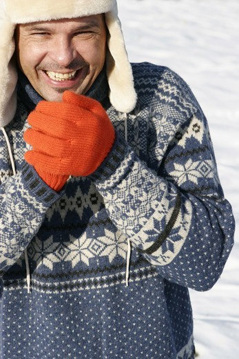 Man with pullover, fur cap and gloves in winter, portrait : Stock Photo