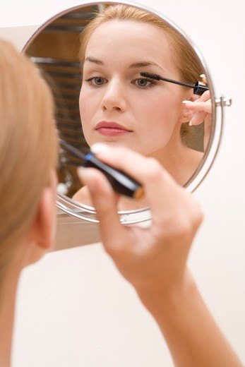 Stock Photo: 4286-70441 Young pretty woman doing makeup, using mascara.