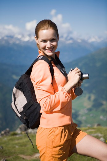 Stock Photo: 4286-70537 Pretty young woman trekking in the mountains and taking pictures.