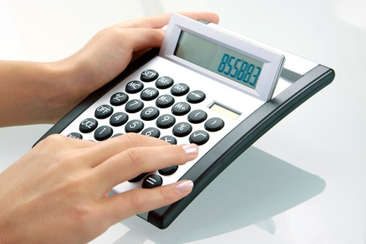 Woman using a calculator : Stock Photo