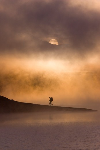 A man hiking along the shore of a misty lake at dawn near Truckee California : Stock Photo