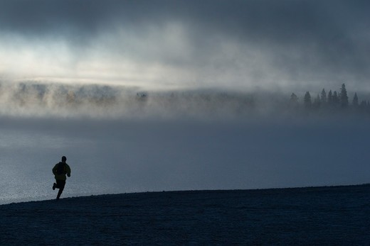 Stock Photo: 4286-72353 A man running along the shore of a misty lake at dawn near Truckee California