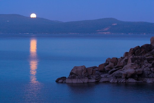 The full moon rising over LakeTahoe at sunset with alpenglow at Lake Tahoe California : Stock Photo