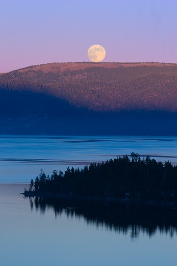 Stock Photo: 4286-72367 The full moon rising over LakeTahoe at sunset with alpenglow at Lake Tahoe California