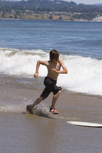 Stock Photo: 4286-72573 A young boy skim boarding on the beach on the Pacific Ocean in Santa Cruz, California