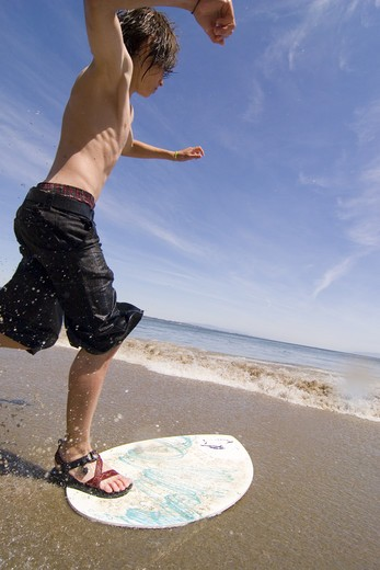 Stock Photo: 4286-72582 A young boy skim boarding on the beach on the Pacific Ocean in Santa Cruz, California