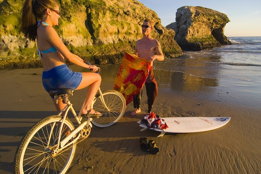 Stock Photo: 4286-72644 A woman on a cruiser bike and a man with a surfboard on the beach at Natural Bridges State Park in Santa Cruz in California