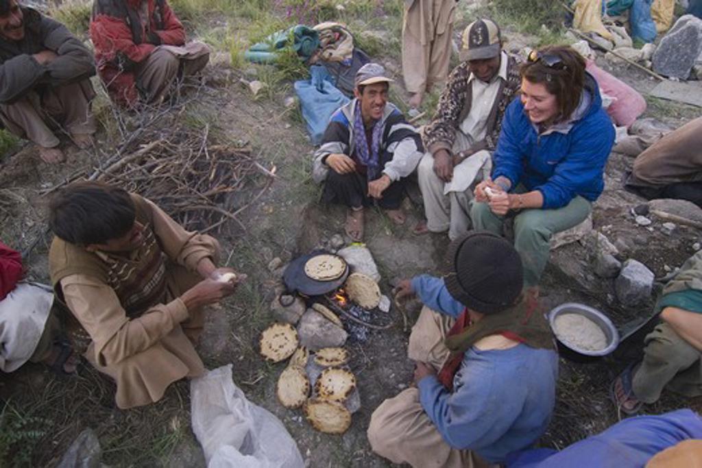 A caucasian woman making chapati bread with some Balti men in Pakistan : Stock Photo