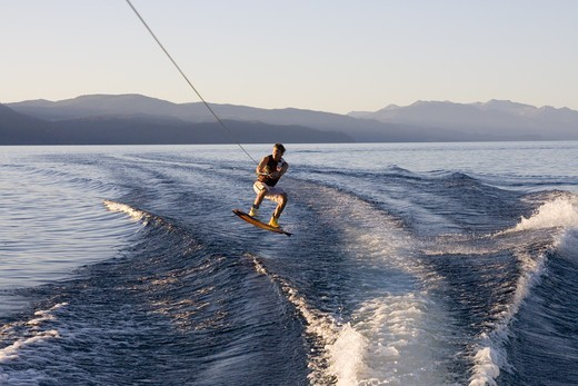 A man wakeboarding at sunrise on Lake Tahoe in California : Stock Photo