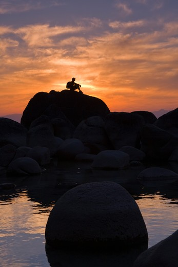 Stock Photo: 4286-72953  A man sitting on a rock on the shore of Lake Tahoe in California at sunset with reflecting water
