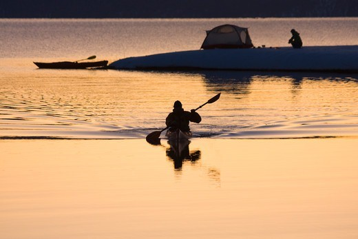 Stock Photo: 4286-73165 A man and his reflection kayaking past a woman and a tent at sunrise in winter on Lake Tahoe California