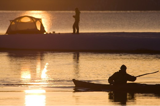 Stock Photo: 4286-73171 A man sea kayaking past a woman camping on the snowy shore of Lake Tahoe in California in winter.