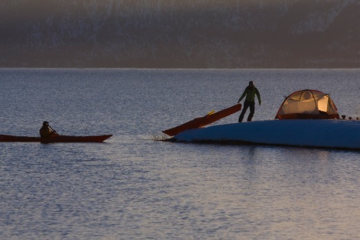 A man sea kayaking past a woman camping on the snowy shore of Lake Tahoe in California in winter. : Stock Photo