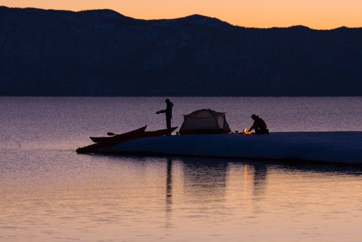 Stock Photo: 4286-73201 A man and a woman sea kayak camping on the shore of Lake Tahoe California in winter at sunrise