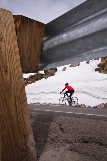 Stock Photo: 4286-73350  A man climbing uphill on a bicyle in winter on Donner Summit in California