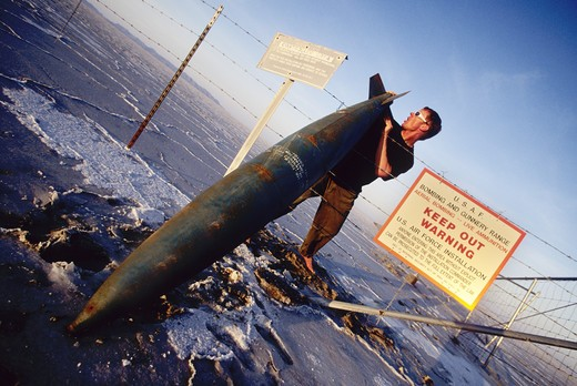 Young man holding old missile at the Bonneville Salt Flats in Utah, USA : Stock Photo