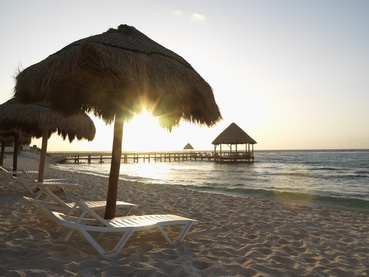Stock Photo: 4286-74117 Mexico Quintana Roo Yucatan Peninsula Akumal Mayan Riviera, beach chairs under palapas at sunrise with pier and palapa jutting out to sea