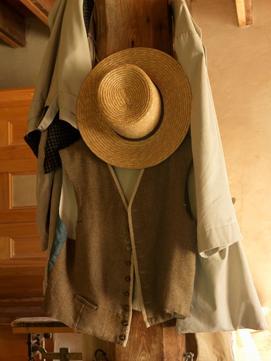 Canada Ontario Morrisburg Upper Canada Village, antique straw hat and vest hanging on a wooden post : Stock Photo