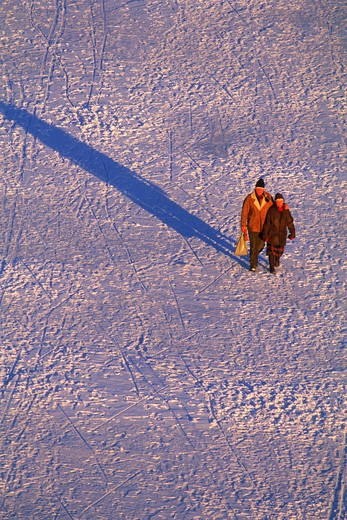 Couple crossing Stockholm on sea of ice in low light of winter : Stock Photo