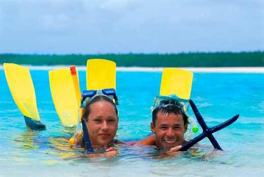 Stock Photo: 4286-74861 Couple with starfish off One Foot Island in Aitutaki lagoon in Cook Islands