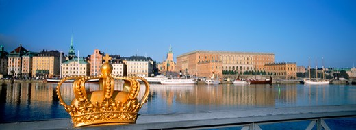 Golden crown on Skeppsholmen Bridge with Royal Palace in Stockholm : Stock Photo