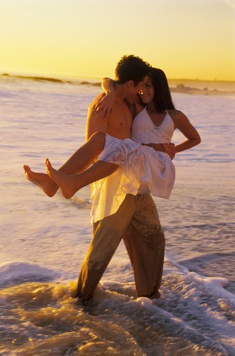 Couple playing in shore surf at sunset : Stock Photo