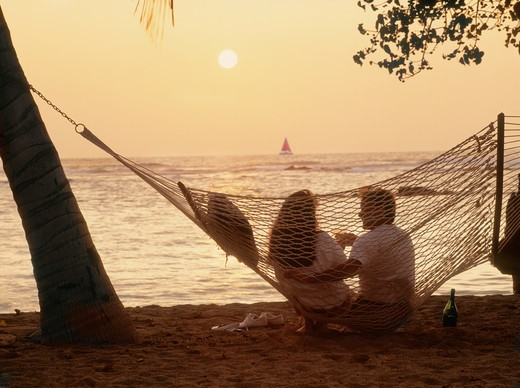 Couple sitting in beach hammock with bottle of Champagne at sunset : Stock Photo