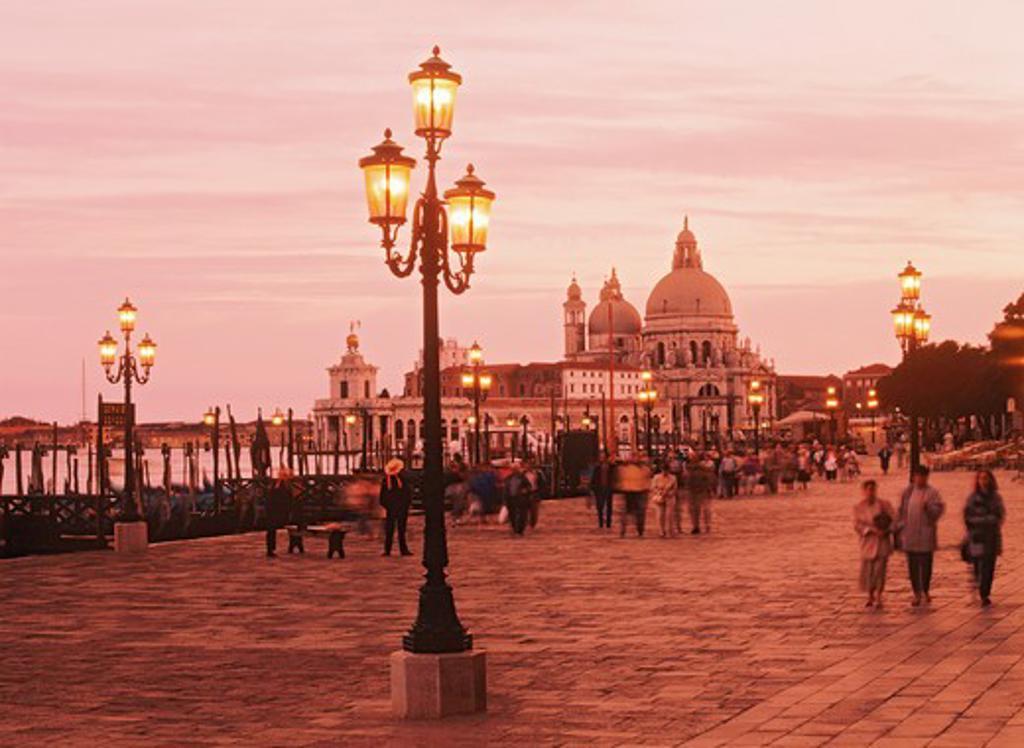 Lamps along St Marks Basin with Santa Maria della Salute church at dusk in Venice : Stock Photo