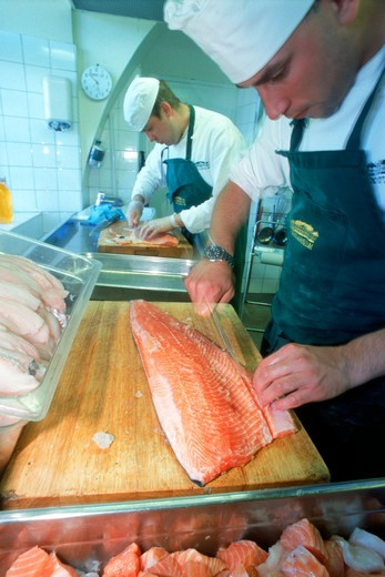 Stock Photo: 4286-75527 Chef in restaurant kitchen filleting fresh salmon on wooden cutting board