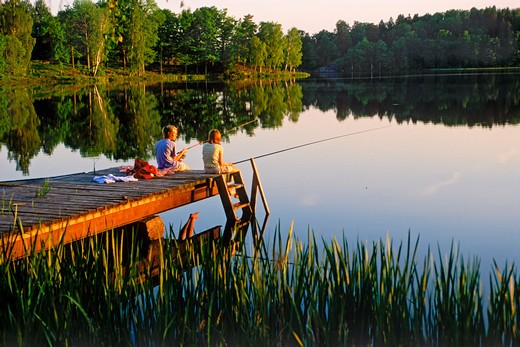 Stock Photo: 4286-75715 Two girls 11 to 13 enjoying fishing picnic on lakeside pier in Sweden at sunset