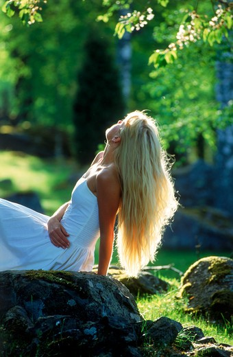 Stock Photo: 4286-75851 Blond woman in white dress relaxing alone in Swedish forest