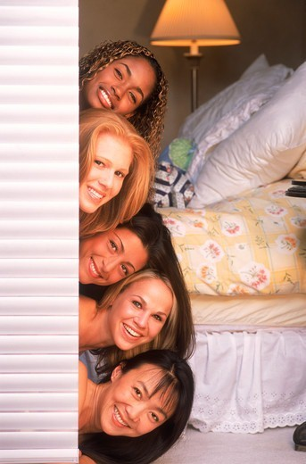 Five women of ethnic mix stacked on top of eachother looking out bedroom door : Stock Photo