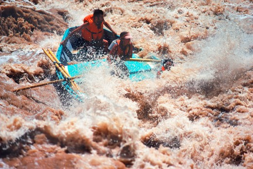 Stock Photo: 4286-76129 Oarswoman guiding Grand Canyon Dory through big churning rapids at Lava Falls on Colorado River