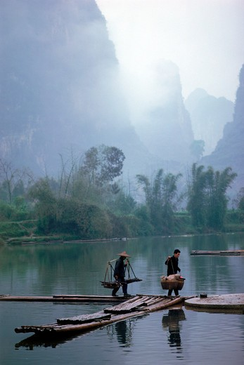 Stock Photo: 4286-76140 Chinese peasants crossing river near Guilin in Yangshuo Guangxi Province in China under moon mountain peaks