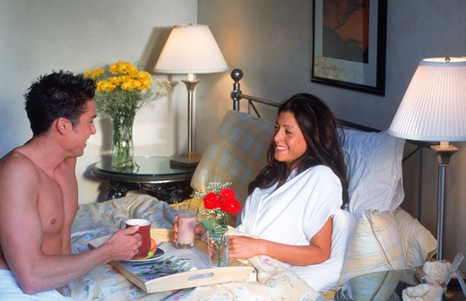 Man serving woman breakfast in bed : Stock Photo