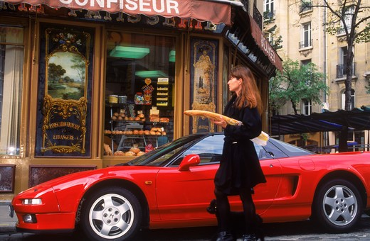 Stock Photo: 4286-76440 Woman in Paris leaving boulangerie with baguette passing red sports car with French poodle on cobblestone street