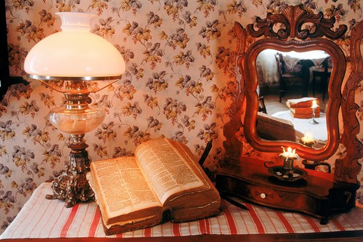 Stock Photo: 4286-76858 Antique wooden bureau with Bible, lamplight and mirror reflecting candle and old bedroom interior in Sweden