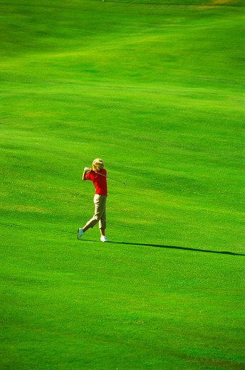 Woman with perfect form hitting iron shot off lush green fairway : Stock Photo