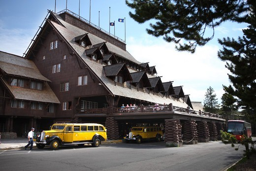 A restored vintage Yellowstone Park tour bus in front of Old Faithful Inn : Stock Photo