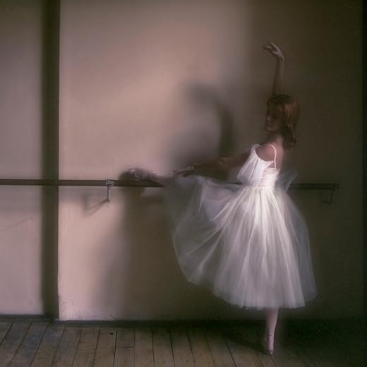 Ballerina rehearsing, left leg on the bar, body straight, right arm extended upwards. : Stock Photo