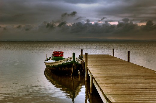 Spain. Valencia. La Albufera Lake. Before the rain starts, a boat moored to the dock. : Stock Photo