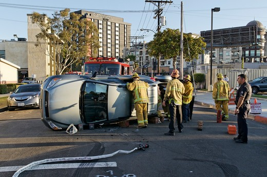 Emergency response professionals have arrived at the scene of a car accident involving a Toyota RAV4 in which five young adults have been trapped as the vehicle ended up on the side, at the intersection of Fordham Avenue and W 85th Street in Westchester, Los Angeles, California : Stock Photo