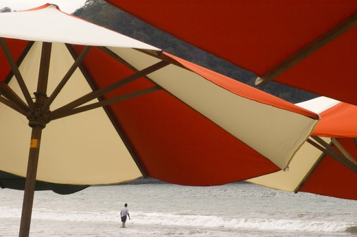Close up of beach umbrellas with a lone man by the shore in La Manzanilla : Stock Photo